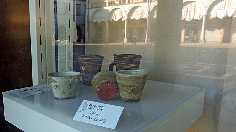 Faenza - Vitrina de Los Productos de Paola Nuovo Con El Fondo de la Piazza del Popolo