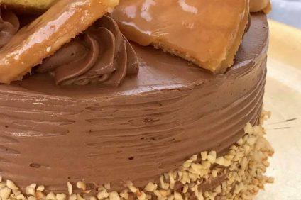 torta Dobos con glassa di cioccolato e decorata con nocciole