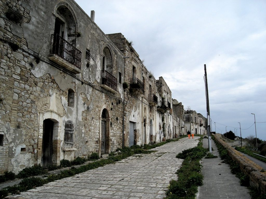 Craco. Immagine di un'antica strada lastricata costeggiata da storici edifici nel borgo di Craco