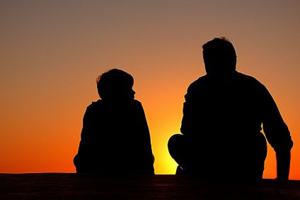 Dad - An orange sky at sunset on which stand the silhouettes of a father with his own child
