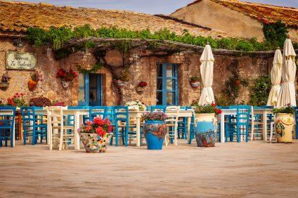 Cucina siciliana - Taverna caratteristica con tavoli e sedie bianchi e azzurri posti all'aperto