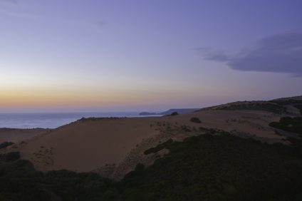 Torre dei Corsari. Desert at sunset with sand dunes under the sky with shades of purple, yellow and orange
