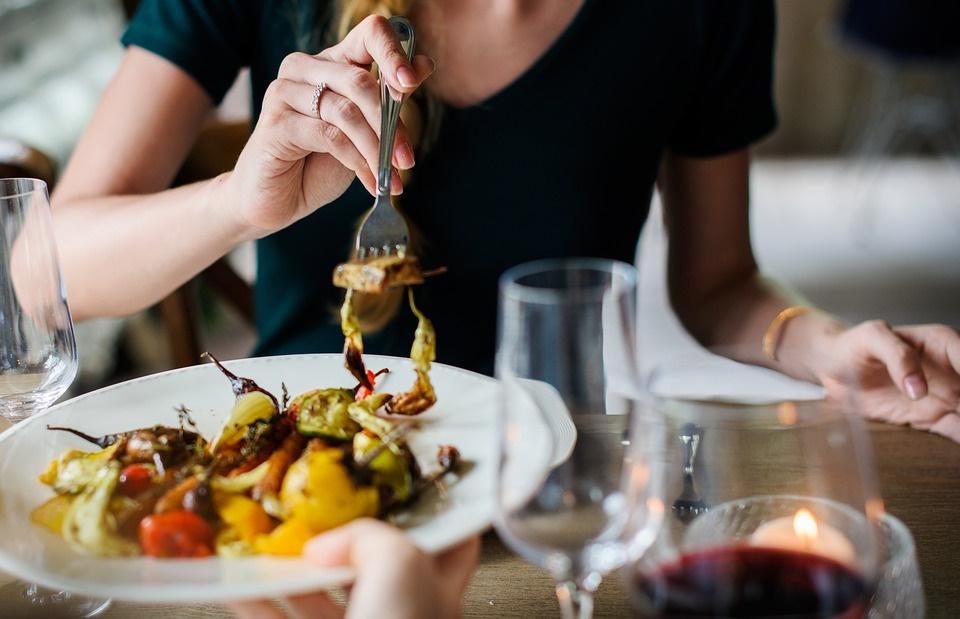 immagine di chef donna seduta a tavola che assaggia una portata