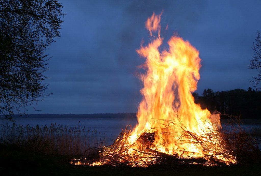 March - image of a fire lit at night in a meadow