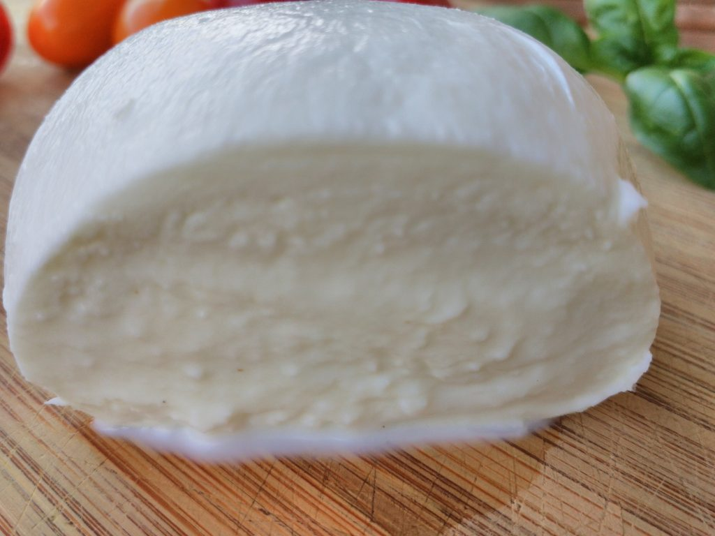 Latin. Buffalo mozzarella with a cut to emphasize the soft heart of milk