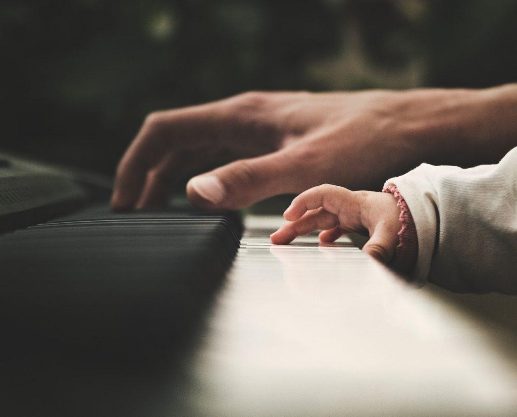 Piero Angela. Tastiera di pianoforte su cui delicatamente si poggia la mano di un adulto e quella di un bambino