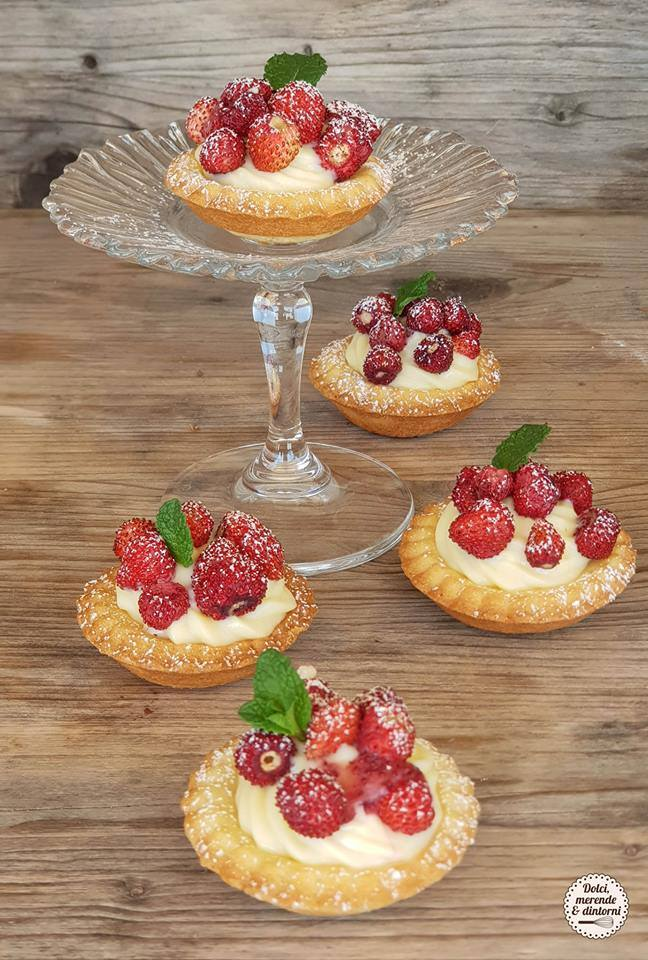 glass top shelf with tartels with custard and wild strawberries