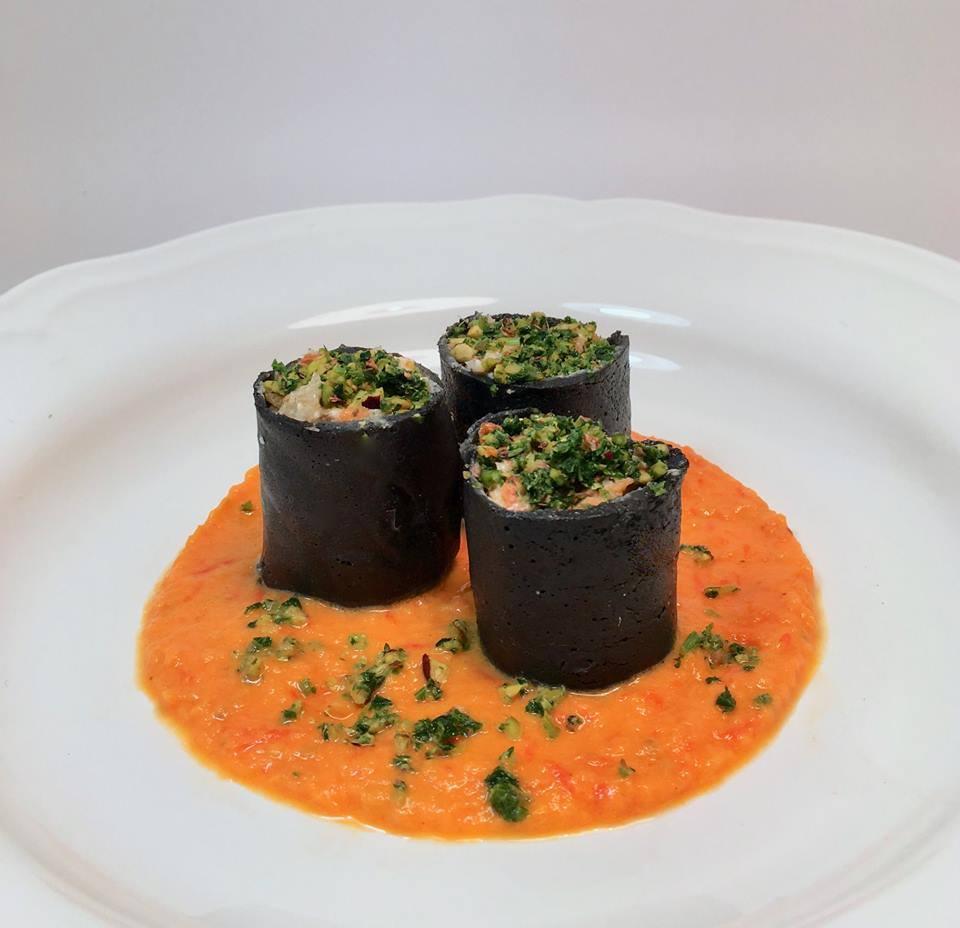 piatto con sughetto con dentro le Crespelle al nero di seppia