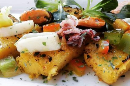 Polenta croutons with 5 cereals with squid and mussels decorated with parsley