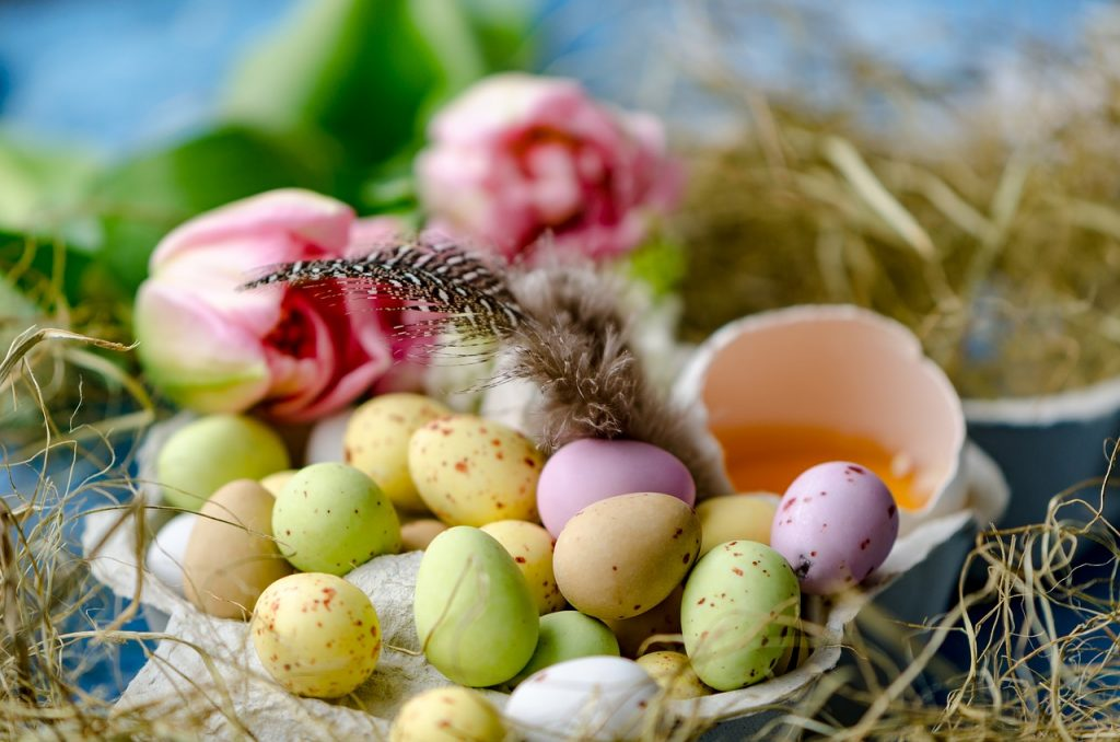 Easter egg. Small eggs painted green, pink and yellow are placed inside a basket laid on straw