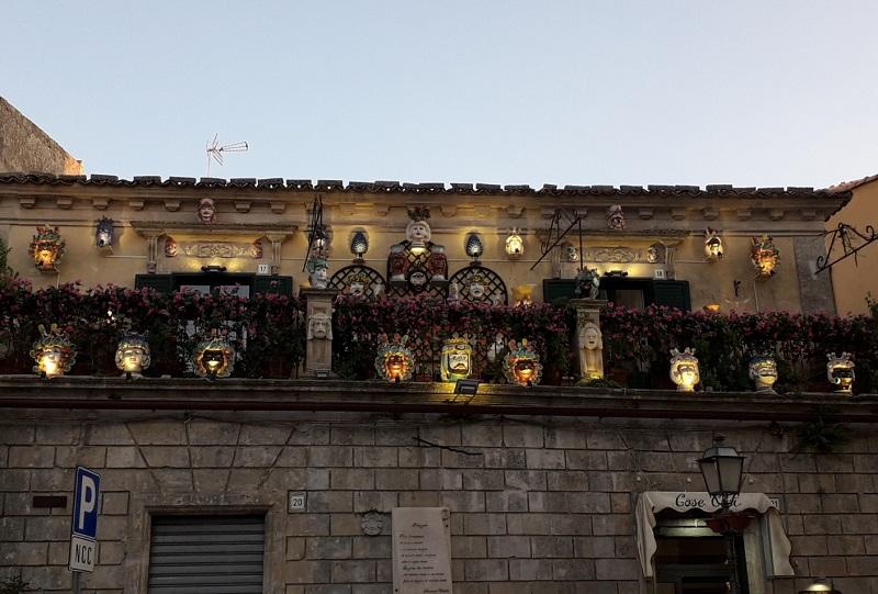 Una balconata di un palazzo siciliano con le tipiche Teste di Moro