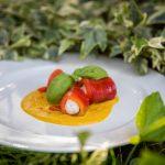 Involtini di peperoni ripieni di persico su piatto bianco