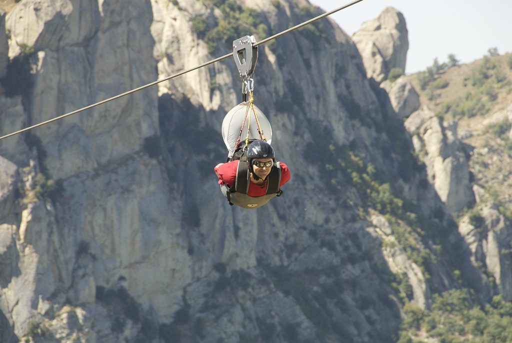 little dolomites.Image of a tourist trying his hand at the flight of the angel anchored to a cable