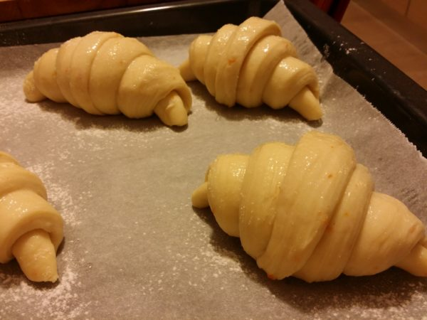 croissants during leavening resting on parchment paper