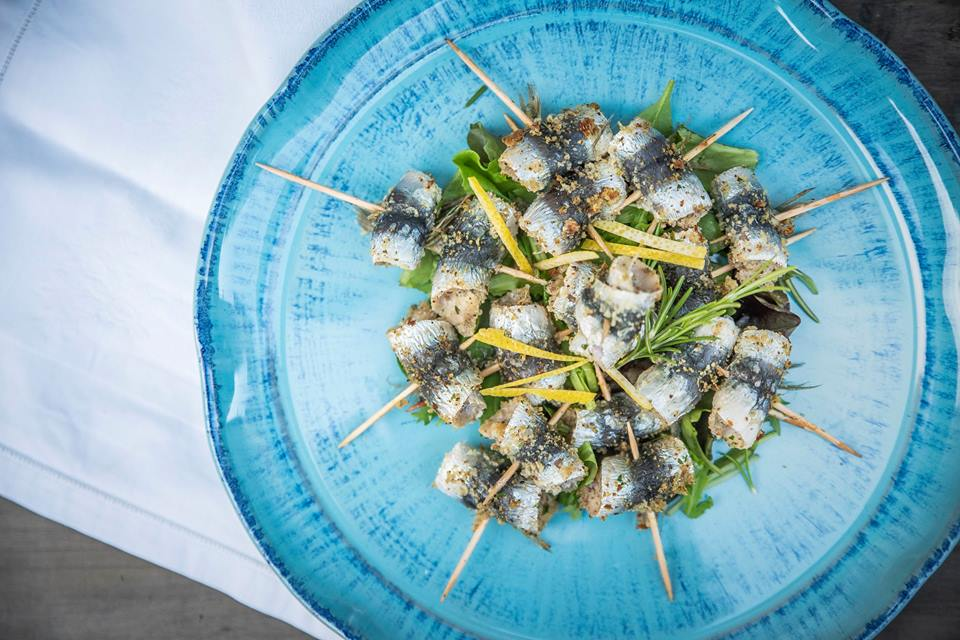 blue plate with gratinated sardines with rosemary