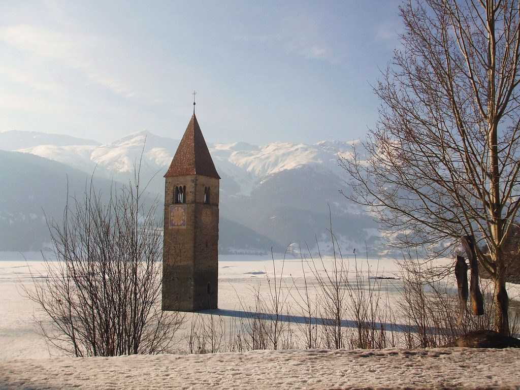 The submerged bell tower. Image of the bell tower of Resia in the snowy landscape