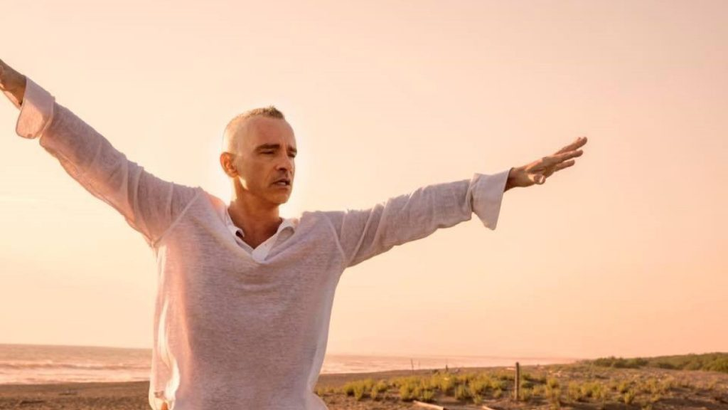 Eros Ramazzotti in white T-shirt with open arms