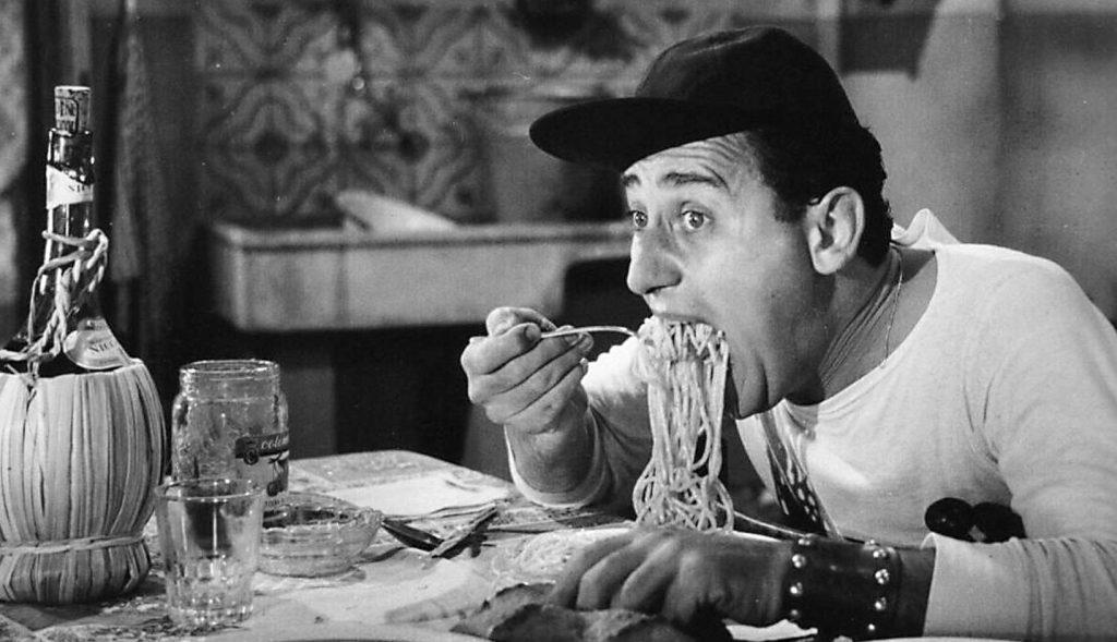 foto di alberto sordi in bianco e nero mentre mangia gli spaghetti
