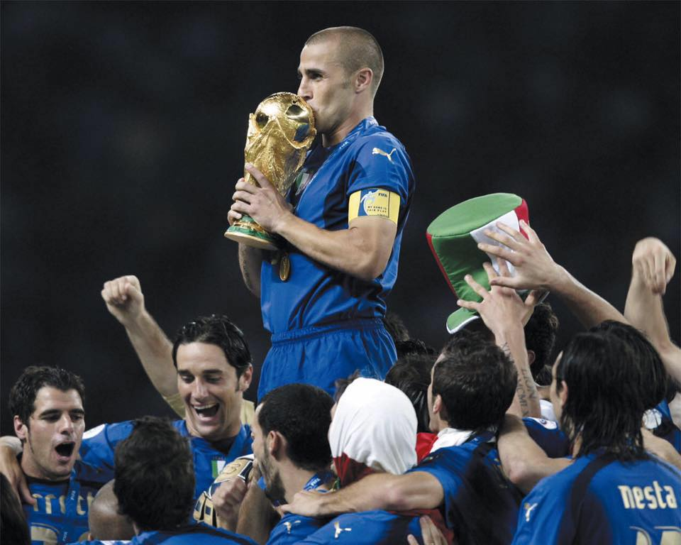 Fabio Cannavaro supported by his companions as he kisses the cup