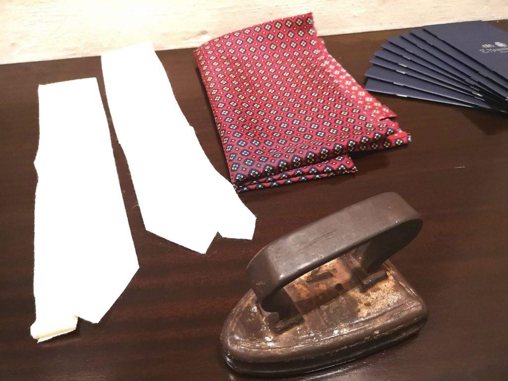 E. Marinella - tavolo con sopra un vecchio ferro da stiro, due modelli di cravatte e una stoffa
