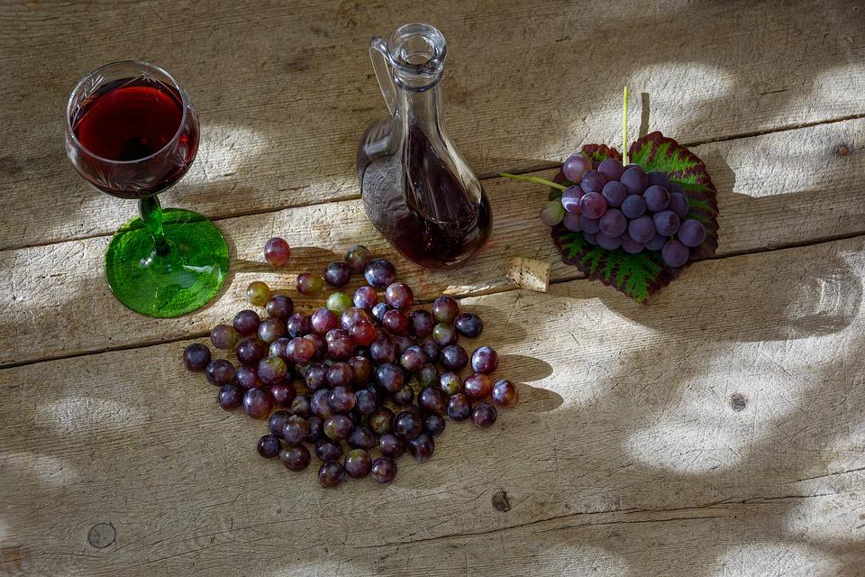 una bottiglia di vino nuovo e grappoli di uva
