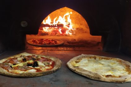 pizza - in the foreground two round pizzas in the wood oven