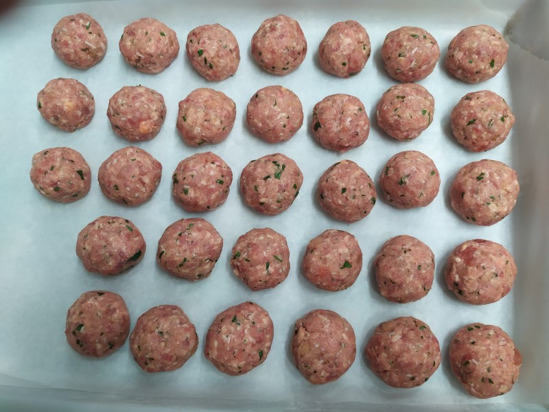 many raw meatballs on parchment paper