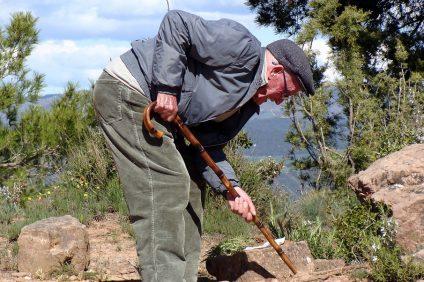 green - un nonno cerca di spostare qualcosa da terra con il suo bastone da passeggio