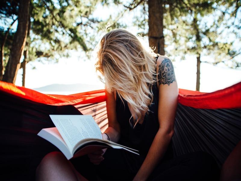 Ragazza in un prato legge un libro in solitudine e con inerzia