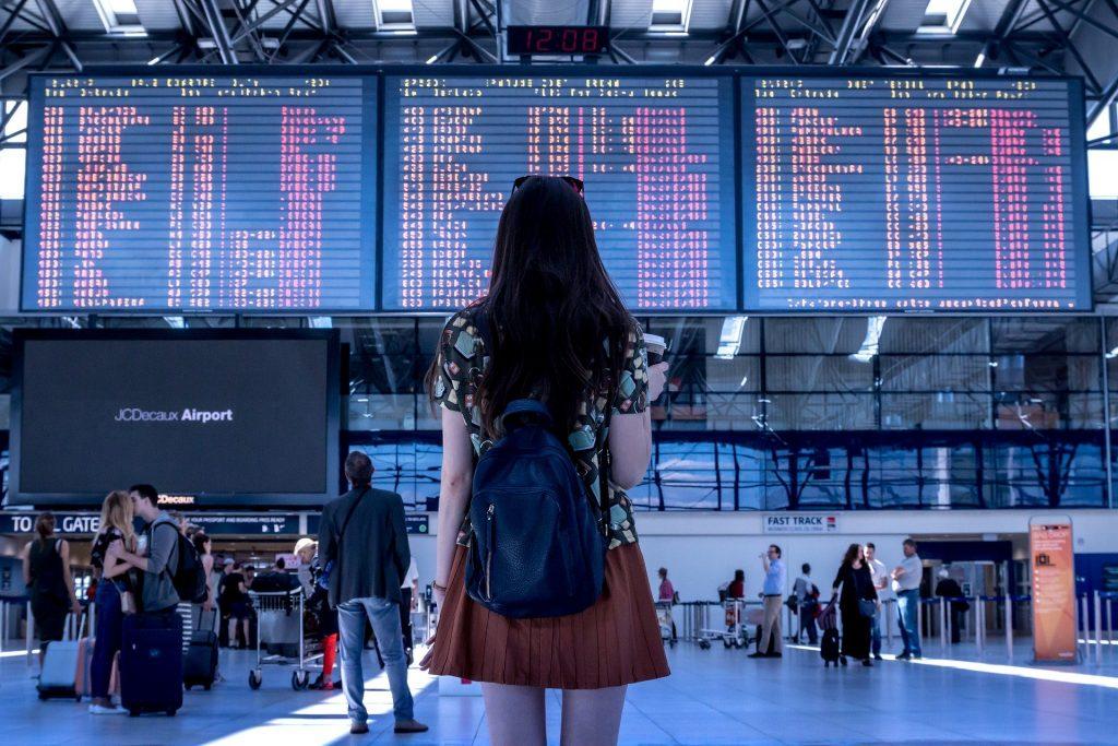 Giada - ragazza di spalle che guarda il tabellone degli orari in aereoporto