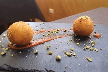 Arancini - due arancini su un piatto nero