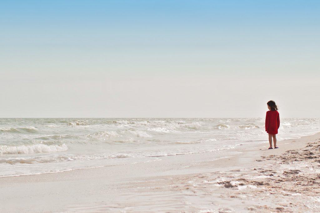 libri - una bambina vestita di rosso in spiaggia