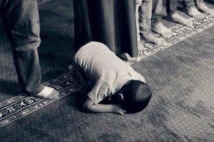 ramadan - foto in bianco e nero di un bambino che prega