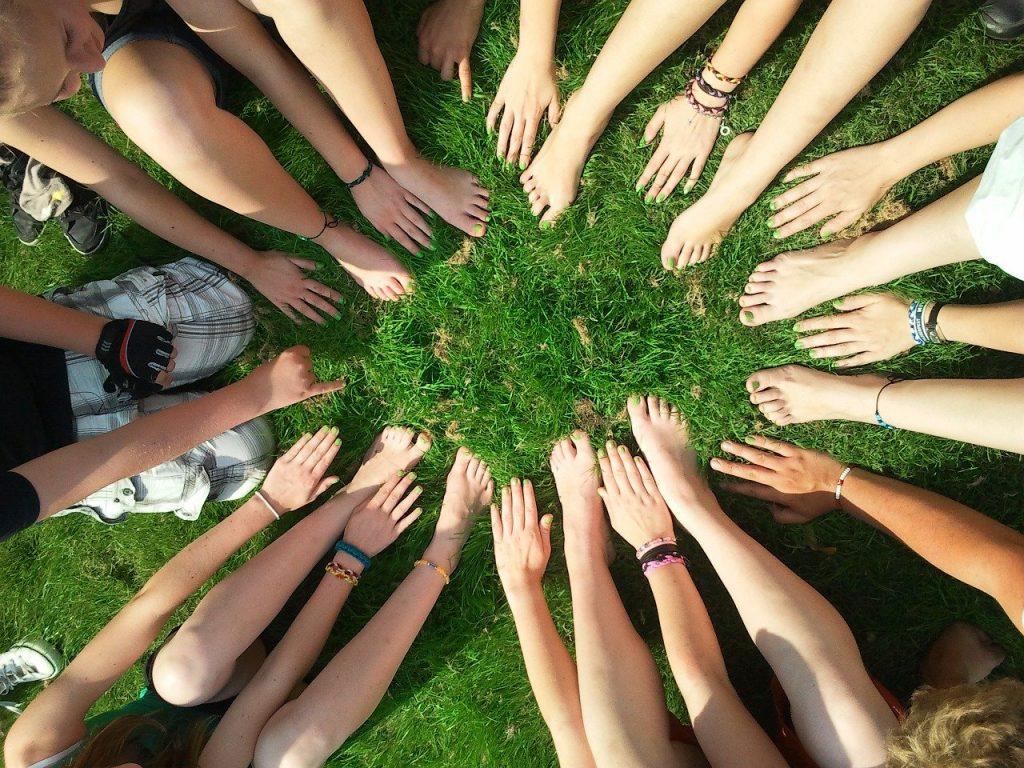 Esperienza tattile di mani e piedi nudi in un prato verde / green