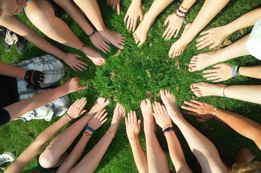 Esperienza tattile di mani e piedi nudi in un prato verde