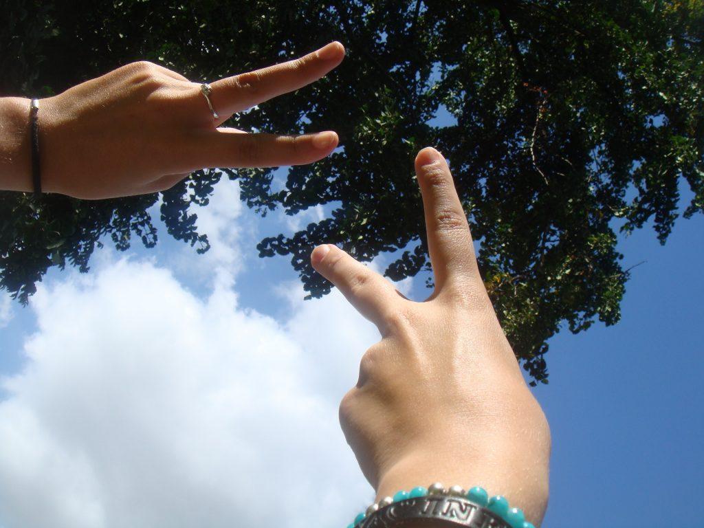 guariti - mani al cielo che indicano il segno della vittoria