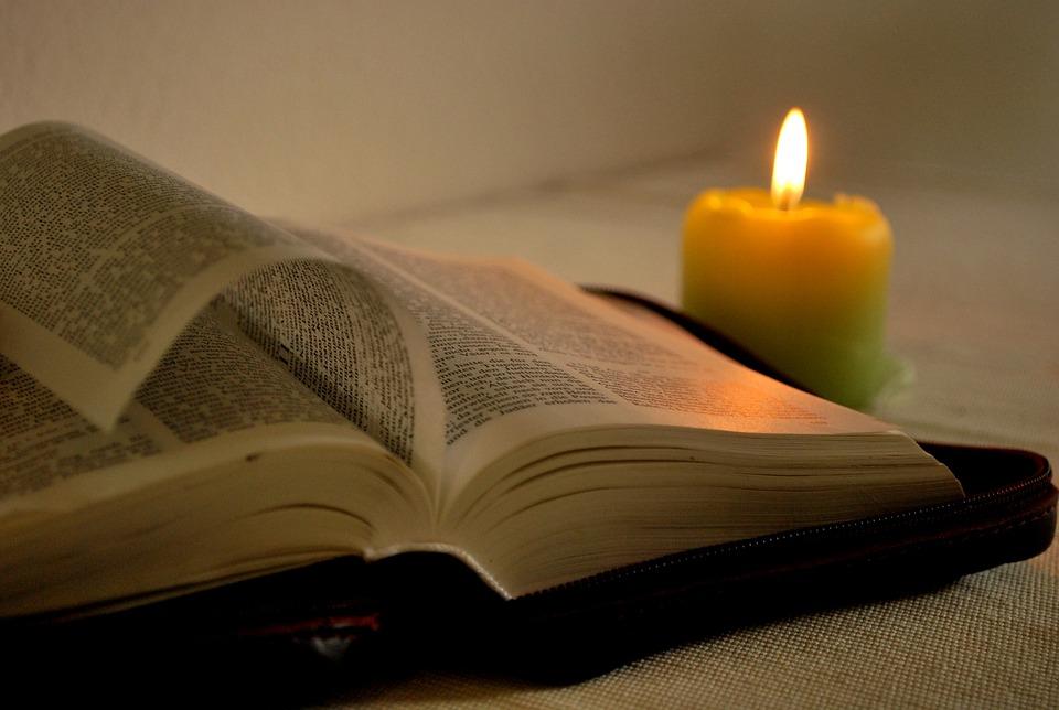 settimana - bibbia aperta con una candela accesa accanto