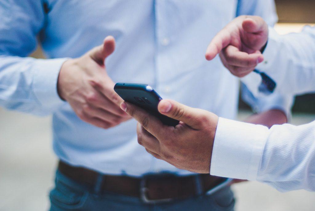 app - due persone che guardano un telefono