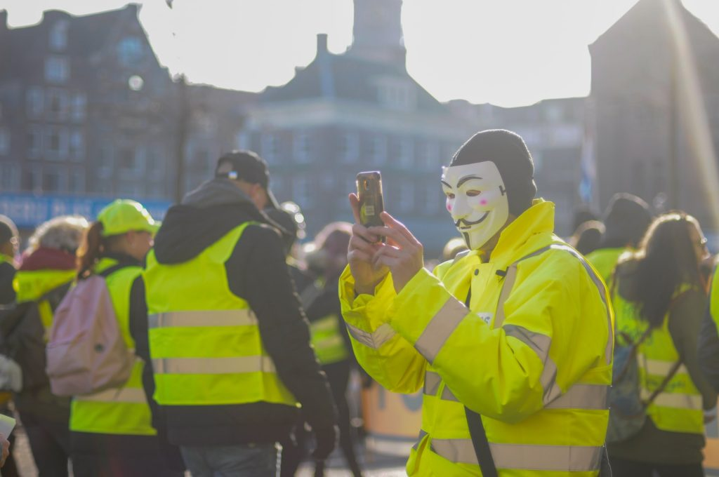 app -  persona in maschera con telefonino  - masked person with mobile phone