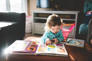 aziende - un bambino che guarda un libro colorato