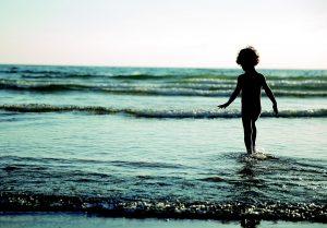 Gli abeti abbattuti - bambino in spiaggia