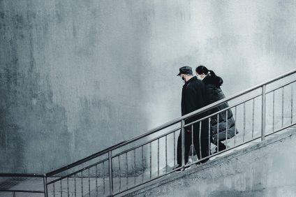 virus - due persone con mascherina che scendono le scale