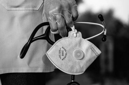 domicilio - foto in bianco e nero di una mano che tiene una mascherina e uno stetoscopio