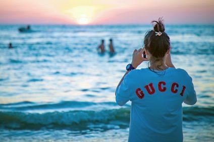moda - ragazza al mare di spalle con maglietta gucci