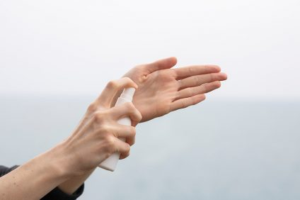 igienizzante - una mano spruzza sull'altra mano un gel igienizzante
