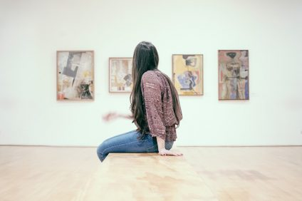 Arte - ragazza seduta che guarda i quadri