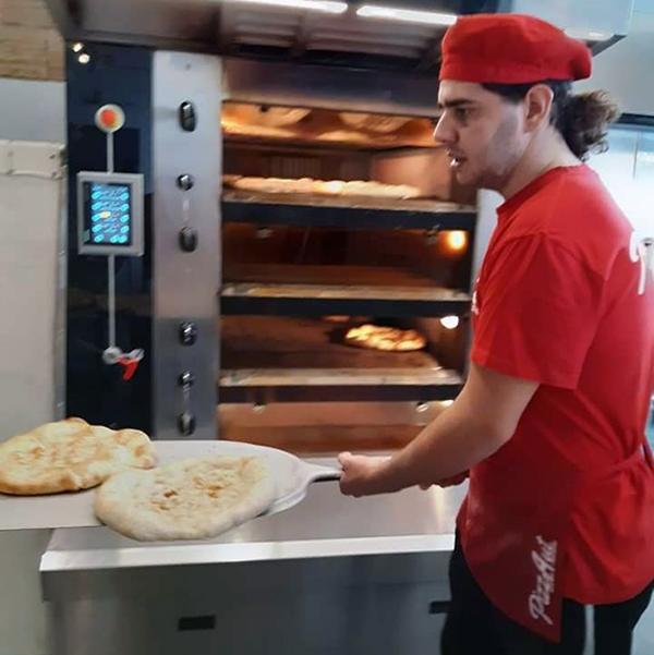 pizzAut - pizzaiolo che inforna una pizza