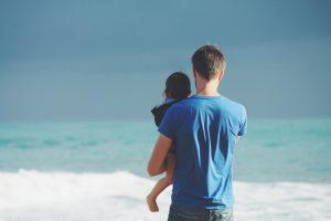 vita - un uomo con bimbo in braccio al mare