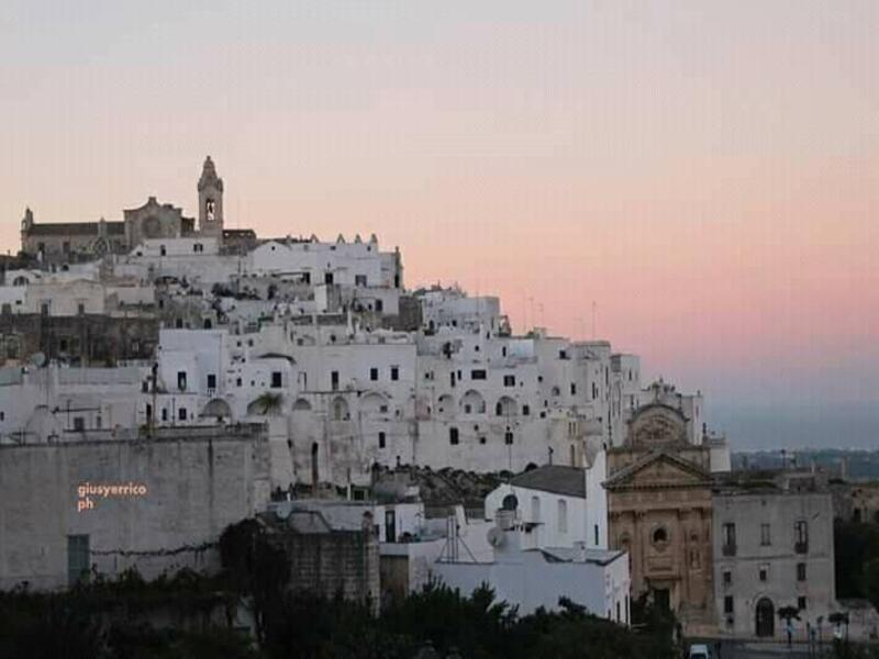 Foto di Ostuni al tramonto col suo centro storico di case bianche - Photo of Ostuni at sunset with its historic center of white houses