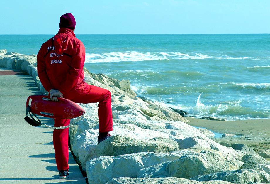 Publiphono - un bagnino vestito di rosso che guarda il mare  - a lifeguard dressed in red looking at the sea